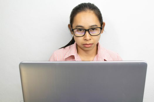 Close up portrait of confident Asian woman, wearing glasses are working with laptop, looking camera with seriously face, sitting over white background with copy space.