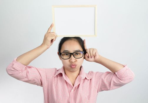 Happy face Asian woman holding blank white board on her head and show finger pointing isolated on a white background. Copy Placed or space for text.