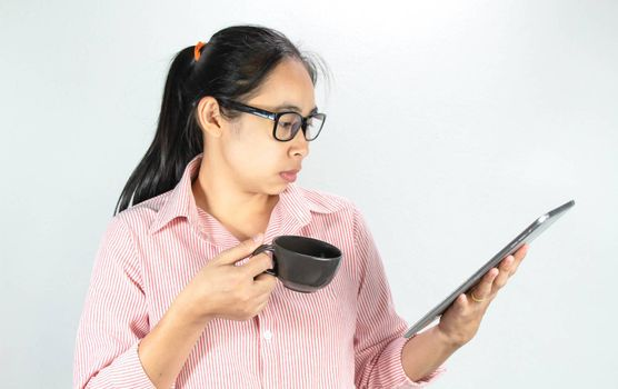Close up portrait of confident Asian woman, wearing glasses and holding coffee cup, looking tablet with looking seriously face, standing over white background with copy space.
