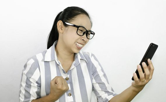 Asian young woman showed a successful gesture while watching her smart phone on white backgroung in room.