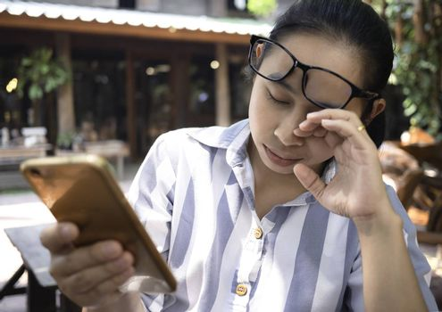 Business Asian young woman holding smartphone do busy with work and has eye problem from using phone for long time.
