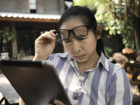 Business Asian young woman holding laptop do busy with work and has eye problem from using laptop for long time.