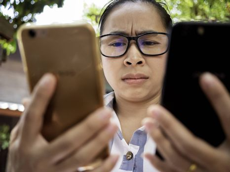 Business Asian young woman holding 2 smartphone do busy with work, Unhappy and worry face.