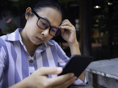 Confidenced business Asian young woman using smartphone at coffee cafe, Serious face.