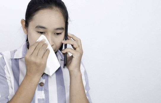 Asian young woman has eyes irritation or eye problemb while talking on the phone, using tissue paper wipe tear.Isolated on white background. Health and medical concept. Space for text.