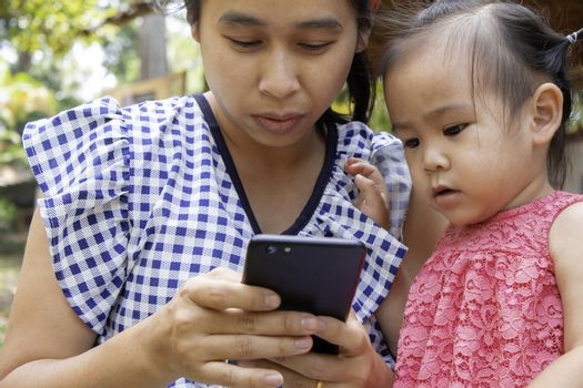 Asian mother and her daughter sitting on the grasses ground in the garden and looking at smartphone happily.