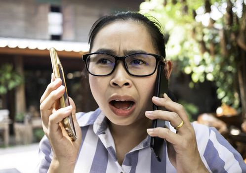 Business Asian young woman holding smartphone do busy with work while talking on the phone simultaneously at coffee cafe.