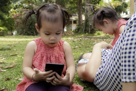Asian little girl sitting on the grasses ground in the garden and looking at smartphone happily while mother and sister lying down to play  near.