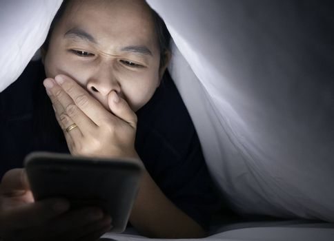 Portrait of Asian woman using smartphone lie about under a white blanket on the bed and have eye pain. Her face is illuminated by a bright monitor. Relaxation time.