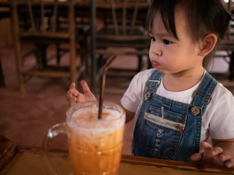 Happy little Asian girl eating thai iced tea with milk in glass at outside of the coffee cafe . Cute face.