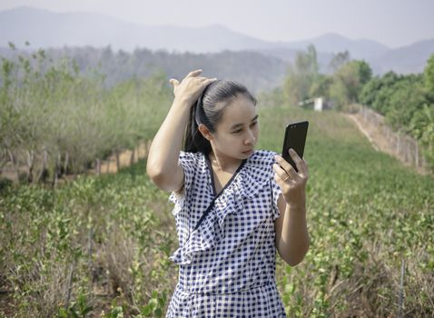 Asian young women talking by video call in the jasmine garden while sunshine to the face.