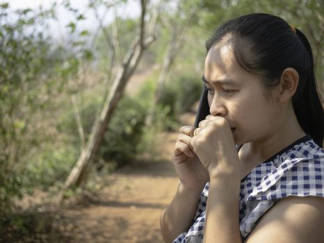 Asian young women talking by phone in the garden and coughing with irritation in the throat.