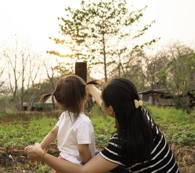 Back view of Asian little child girl taking a photo with mother in garden over sunset background.