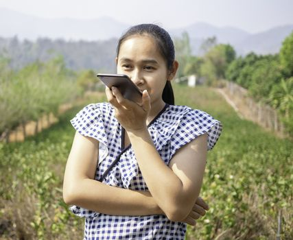 Asian young women talking by speaker phone in the jasmine garden while sunshine to the face.