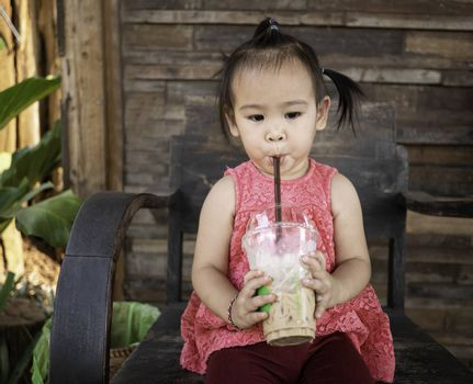Happy little Asian girl sitting on wooden chair and eating thai iced tea with milk in plastic glass at outside of the coffee cafe . Cute face.