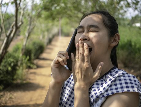 Asian young women talking by phone in the garden and yawn while sun shines  to the face.