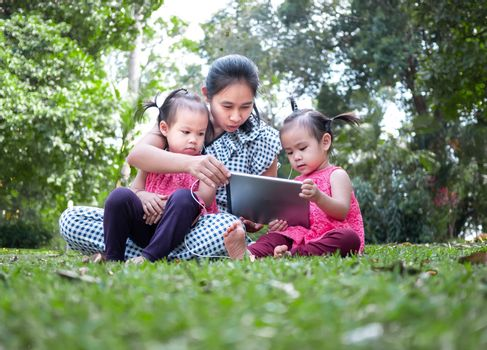 Asian mother and her daughters sitting on the grasses ground in the garden and looking at digital tablet happily.