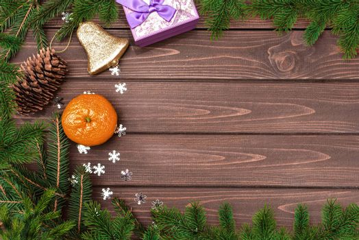 Christmas background, Fir branch, cones , orange, bell and gifts on a wooden table. Space for text. View from above. Christmas atmosphere