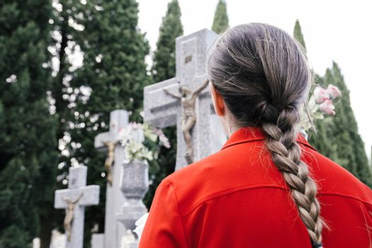 Woman with red blouse and hair braid praying to a loved one at the cemetery