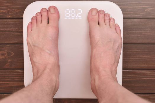 men's feet on an modern electronic scales. sports concept