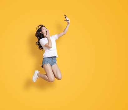 young woman jumping while watching the mobile phone