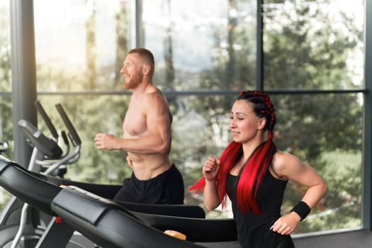 Gym treadmill running trainer man woman training together jogging fitness workout Warming up before functional cross training Personal coach train girl run on treadmil with panoramic window background