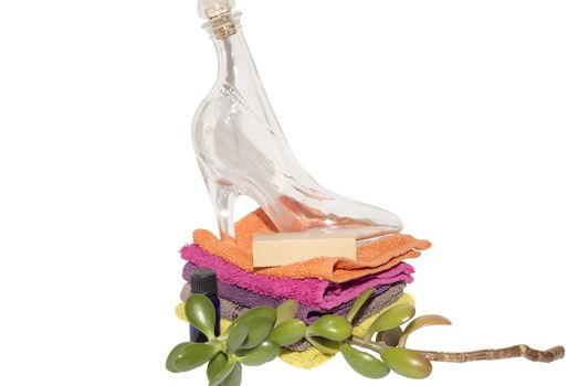glass shoe and soap on facecloths of various shades with natural green plant