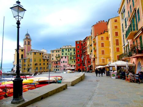 Liguria, Italy - 06/15/2020: Travelling around the ligurian seaside. Panoramic view to the seaside and the old villages. An amazing caption of the medieval coloured houses with grey sky in the background.
