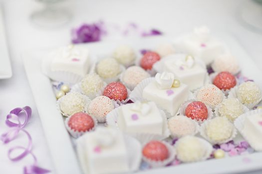 Decorated colorful candies on a white plate