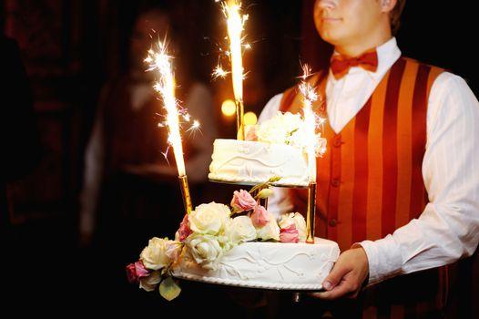 Waiter carrying wedding cake in a dark