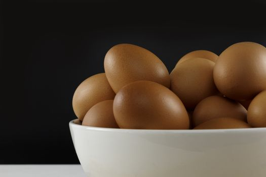 Close up fresh chicken eggs on linen tablecloth and white table with copy space .