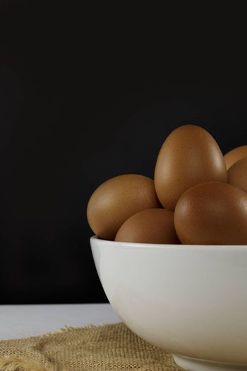 Close up fresh chicken eggs in white bolw on linen tablecloth and white table with copy space .