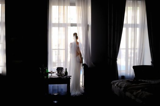Bride standing against the window