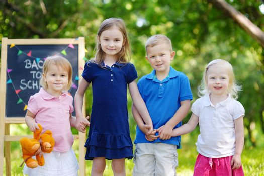 Four adorable little kids feeling very excited about going back to school