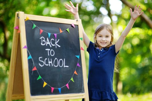Adorable little schoolgirl feeling very excited about going back to school
