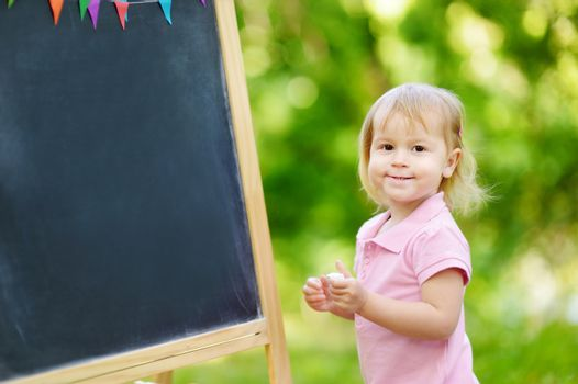 Adorable toddler drawing with a chalk on a blackboard