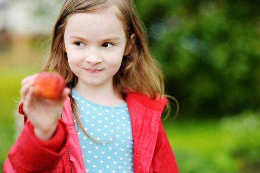 Cute little girl holding a ripe strawberry