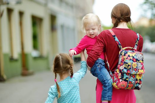 Young mother and her two cute daughters walking down the street on a summer day