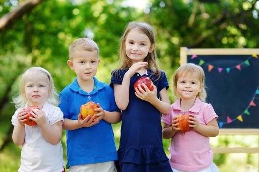 Four adorable little kids holding heathy organic apples in summer park on beautiful sunny day