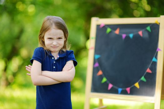 Adorable little girl feeling unhappy about going back to school