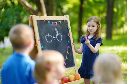 Adorable little girl playing a teacher standing by a blackboard in front of her little students