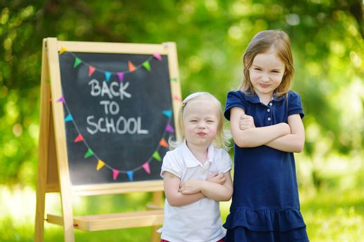 Two adorable sisters feeling unhappy about going back to school