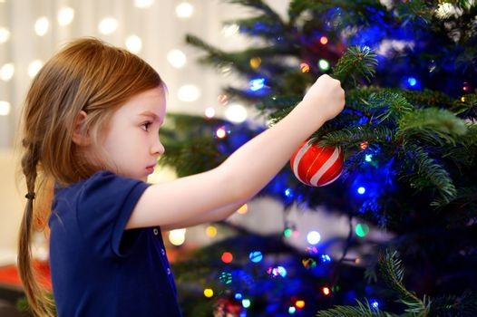 Little girl decorating a Christmas tree