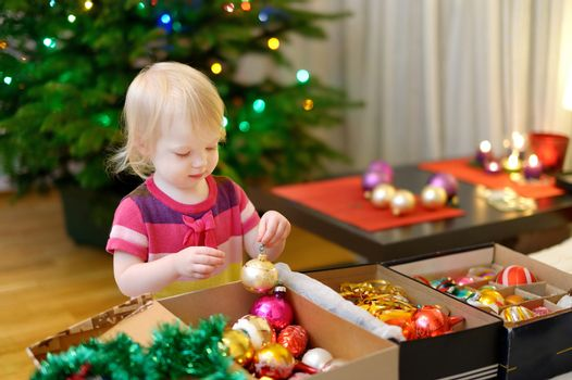 Adorable little girl decorating a Christmas tree