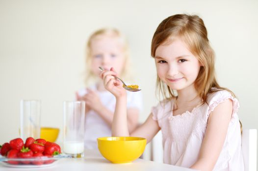 Two sisters eating cereal with milk