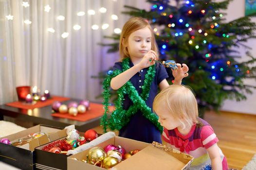 Two little sisters decorating a Christmas tree