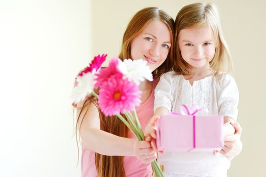 Young mother and her little daughter giving a gift wrapped in pink wrapping paper and flowers