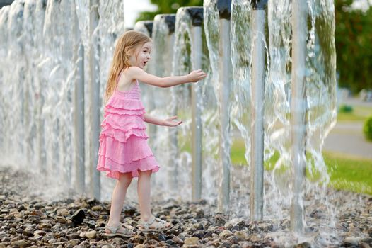 Cute girl playing with a city fountain