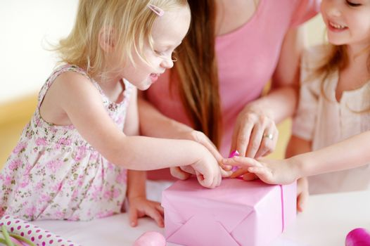 Young mother and her two little daughters wrapping a gift with pink wrapping paper