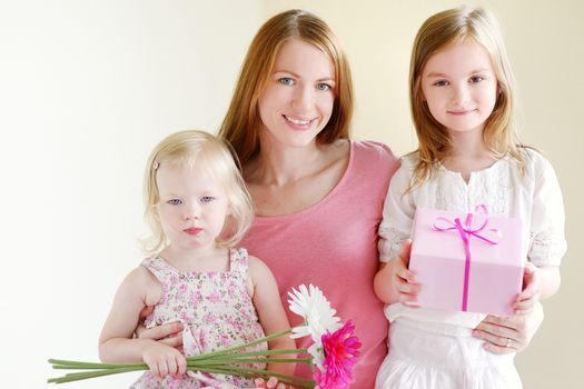 Mother and he daughters giving a gift